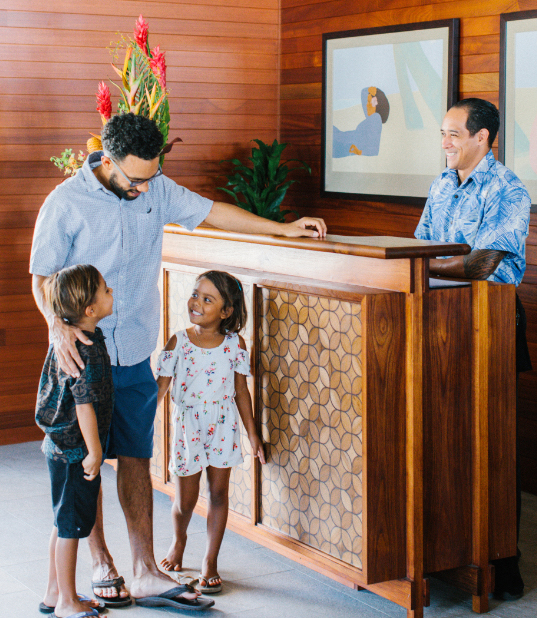 Family of three checking in with the front desk host