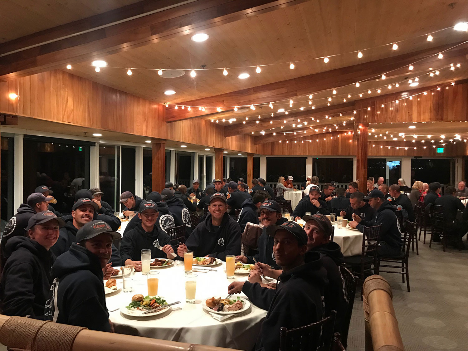 Group of firemen eating dinner in large open indoor room